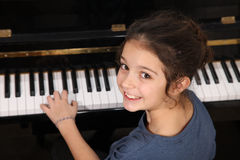 Piano lesson. Young girl sitting at a piano keyboard royalty free stock images
