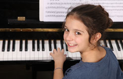 Piano lesson. Young girl sitting at a piano keyboard stock image