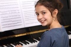 Piano lesson. Young girl sitting at a piano keyboard royalty free stock image