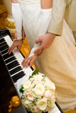 Piano lessons. Groom holding bride fingers over piano keyboard Royalty Free Stock Images