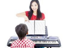 Piano lessons. Young boy taking piano lessons at home with his tutor Royalty Free Stock Photo