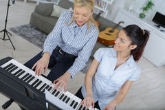 Piano lessons at music school teacher and student. Piano lessons at a music school teacher and student Stock Photos