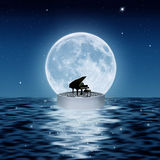 The piano and the moon. A piano on a platform floating in the sea at the moonlight