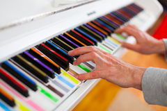 Piano with multy coloure keys. Close up. Lerning to Play white piano with multy coloure keys Stock Photo