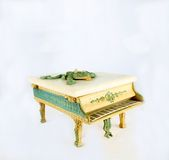 Piano Music Box. Isolated antique piano music box with white marble top and trimmed in pastel green royalty free stock photography