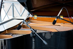 Piano with open lid. two microphones above the strings of black Royalty Free Stock Photography