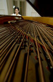 A Piano and a Pianist. Interesting perspective on the strings and internal mechanism of an open grand piano with a female pianist in the background Stock Photo
