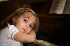 Piano player 1. A little girl not wanting to play the piano Stock Image