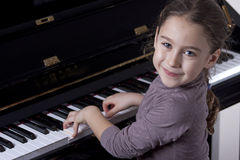 Piano player. A young pianp players is smiling to us as her hands are on the keyboard Royalty Free Stock Image