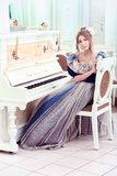 Piano player. Beautiful young woman in medieval era dress playing the piano Royalty Free Stock Photography