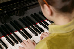 Piano Player. A over-the-shoulder shot of a young girl playing the piano. Focus is on her hands and the keyboard stock image
