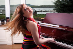 Piano Player. Beautiful young woman playing the piano Stock Photography