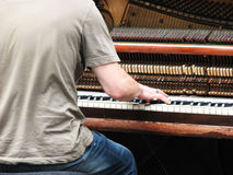 Piano player. Busker playing old upright piano in city center Stock Image