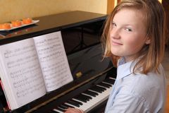 Piano player. Young blond girl plays piano Stock Image