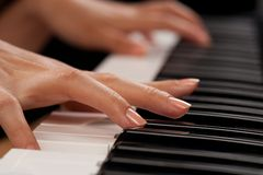 Piano player closeup on hands. Close up of the hands of a young woman playing piano Royalty Free Stock Image