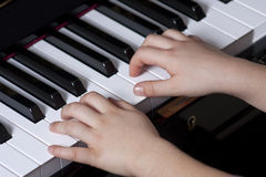Piano player detail. A young pianp players hands are on the keyboard Stock Photos
