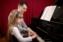 Piano player and his little girl student during lesson Royalty Free Stock Photo