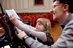 Piano player and his little girl student during lesson. Father teaches young daughter playing piano Royalty Free Stock Photo