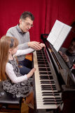 Piano player and his little girl student during lesson. Father teaches young daughter playing piano Stock Photos