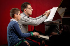 Piano player and his student during lesson. Father teaches his young son playing piano Stock Image