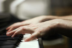 Piano player`s hands. Close up of a man`s hands playing the piano with blurred background Royalty Free Stock Photography