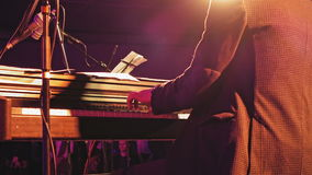 Piano player on the stage. Piano player plays the piano keyboard on the stage with sound lights. Jazz retro vintage concert performance entertainment. Close up stock footage
