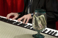 Piano player with tips jar Stock Image