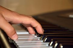 Piano playing. Detail of kid playing on the piano with hand Stock Image