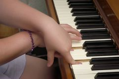 Piano Practice. Young girl's hands crossed on keys during playing of the piano Royalty Free Stock Photography