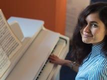 Piano praticando de sorriso feliz novo da mulher caucasiano Imagem de Stock Royalty Free