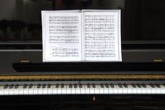 Piano preto com música de folha Fotos de Stock Royalty Free