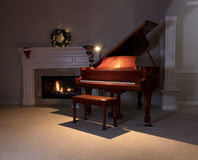 Piano with reading light and glowing fireplace during holiday se Royalty Free Stock Images