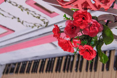 Piano with red roses. Vintage piano with red bouquet of roses royalty free stock images