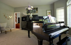 Piano In Residential Home. Residential home front room featuring a large black piano Stock Image