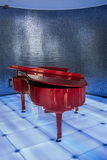 Piano rouge sur la scène bleue de club Photographie stock libre de droits