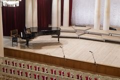 Piano on scene and empty chairs in the concert hall royalty free stock image