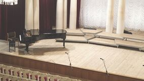 Piano on scene and empty chairs in the concert hall stock photo