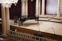 Piano on scene and viewers in the concert hall royalty free stock photos