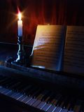 Piano and sheet music in the candle lighting. Piano and opened book with sheet music stock image