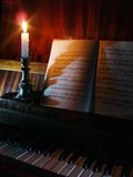 Piano and sheet music in the candle lighting. Piano and opened book with sheet music stock photography
