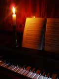 Piano and sheet music in the light of candle. Piano and opened book with sheet music Royalty Free Stock Images