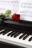 Piano with Sheet Music and a Rose. Sheet music with rose on piano royalty free stock images