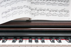 Piano and sheet music. Music sheet on the wooden piano keyboard stock image