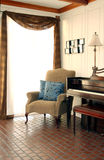 Piano in Sitting Room. A piano and chair sit next to each other in a sitting room with a lot of sun coming through the window and curtains Stock Photos