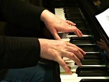 piano som leker den höga kvinnan Nära övre sidosikt av äldre händer och fingrar som spelar en sång royaltyfria bilder