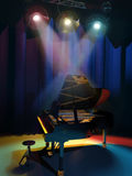 Piano on stage. A stool in front of a piano ready to be played under the stage spotlights Royalty Free Stock Images