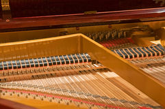 Piano strings and hammers. A view looking into the inner strings and hammers of a baby grand piano Royalty Free Stock Photos