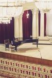 Piano sulla scena e sedie vuote nella sala da concerto immagine stock
