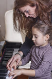 Piano teacher. A piano teacher is showing a note to her young student royalty free stock image