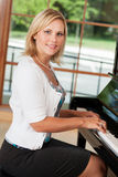 Piano teacher. A beautiful piano teacher sitting at a piano Stock Photography